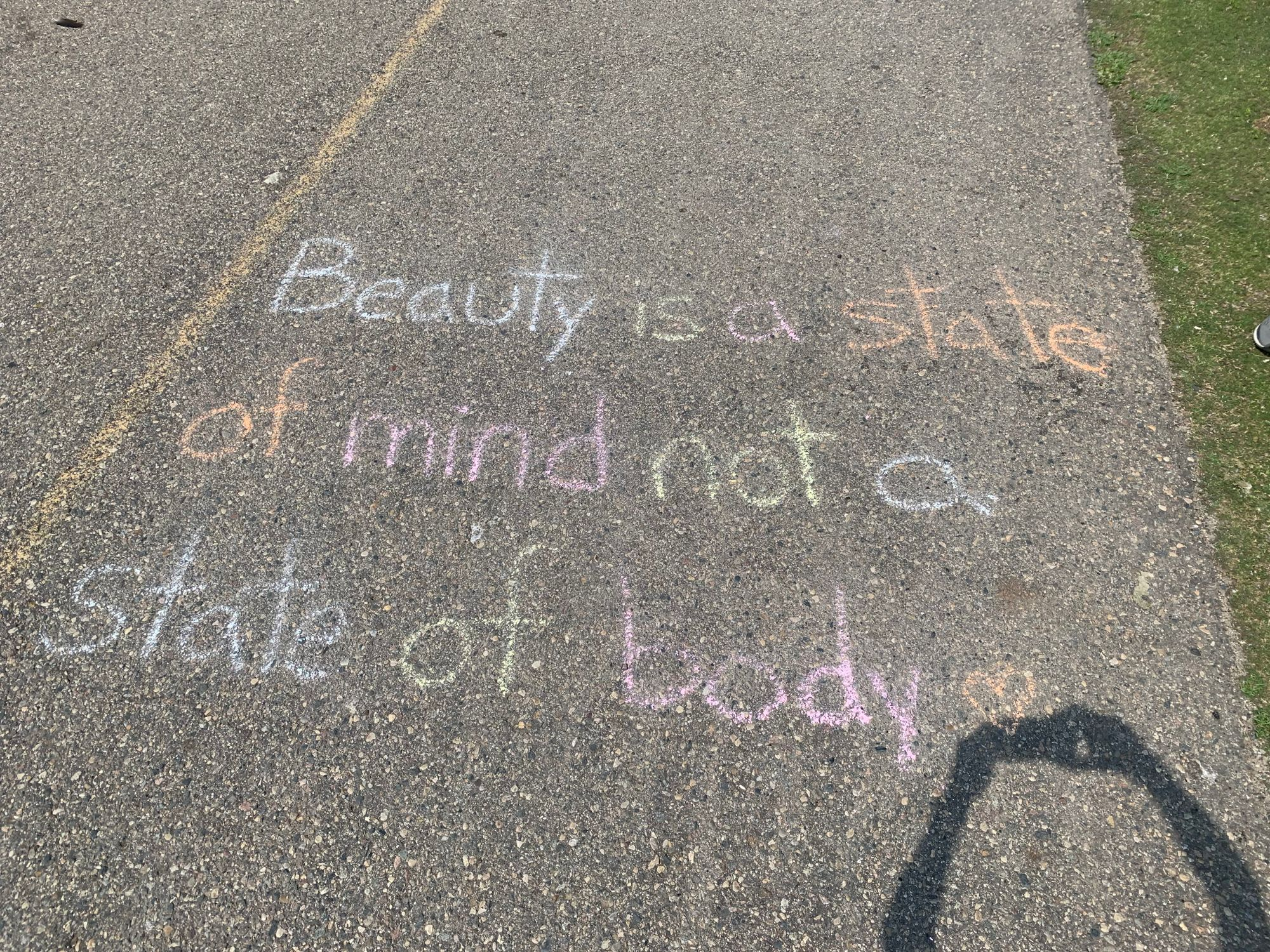 """""""Beauty is a state of mind not a state of body,"""" written in chalk on the sidewalk."""